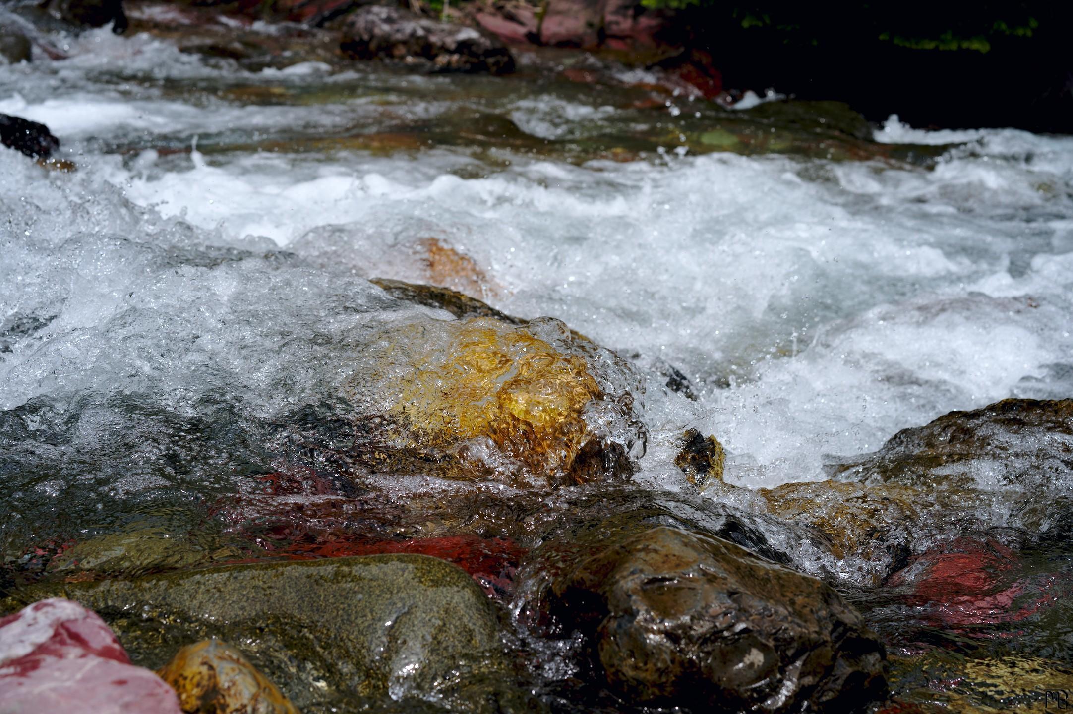 Water rushing over orange-y rock