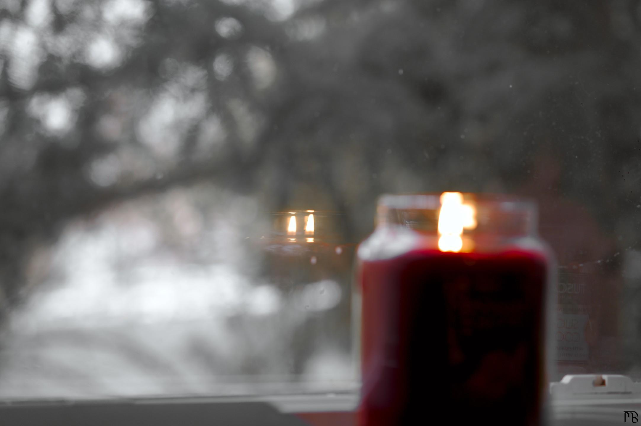 Arty red candle with flame in window reflection